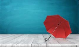 rendu 3d d'un parapluie ouvert de rouge simple se trouvant de son côté avec un auvent ouvert sur une surface en bois sur le fond  Images libres de droits