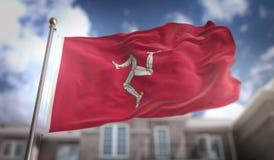 Rendu du drapeau 3D d'île de Man sur le fond de bâtiment de ciel bleu Photo stock