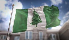 Rendu du drapeau 3D de l'Île Norfolk sur le fond de bâtiment de ciel bleu Image libre de droits