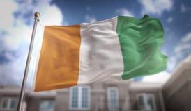Rendu du drapeau 3D de la Côte d'Ivoire sur le fond de bâtiment de ciel bleu Photo stock