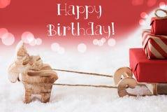 Renen med släden, röd bakgrund, smsar lycklig födelsedag Arkivfoton