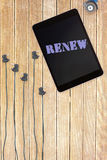 Renew against tablet and plugs on wooden background Royalty Free Stock Image
