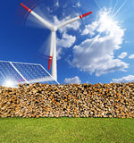 Renewable Energies Concept. Solar panels, firewood logs in a pile and a turbine power station - renewable energy Stock Images