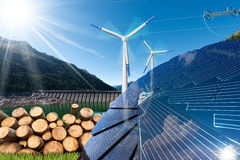 Renewable Energies - Wind Solar Biomass Hydropower. Renewable energies sources - Wind energy wind turbines,  solar energy solar panels, biomass tree trunks and Stock Photography