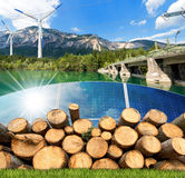 Renewable Energies - Wind Solar Biomass Hydropower. Renewable energies sources - Wind energy wind turbines,  solar energy solar panels, biomass tree trunks and Stock Photos