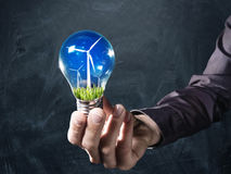Renewable energy concept. Hand holds a light bulb with green grass and a windmill inside on a chalkboard background Stock Photo
