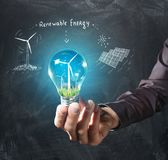 Renewable energy concept. Hand holds a light bulb with green grass and a windmill inside on a chalkboard background Royalty Free Stock Photo