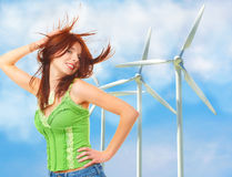Renewable energy concept. Wind turbines. Renewable energy concept, with happy girl in foreground and wind turbines in the background. Notice a little recycling Stock Image
