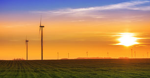 Renewable energy concept, windmills at sunset Royalty Free Stock Photos