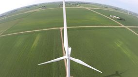 Renewable energy ecology wind power green farm field with big white windmill turbine in stunning 4k aerial drone view. Energy ecology renewable wind power green stock video footage