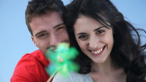 Renewable energy. Happy smiling couple playing with a toy windmill outdoor, symbol of environmental conservation and renewable energy. Portrait of joyful young stock video footage