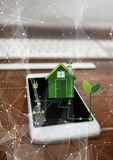 Renewable energy house on phone. Digital composite of renewable energy house on phone Royalty Free Stock Photos