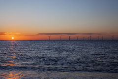 Renewable energy - offshore wind farm at dawn. Renewable energy, An offshore wind farm in the red glow of dawn. These turbines caught at sunrise off the East Royalty Free Stock Photos