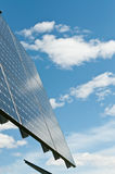 Renewable Energy - Photovoltaic Solar Panel Array. A photovoltaic solar panel array with a blue sky and puffy white clouds in the background Royalty Free Stock Photography