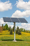 Renewable Energy - Photovoltaic Solar Panel Array. A photovoltaic solar panel array in a park with a blue sky and puffy white clouds in the background Royalty Free Stock Photos