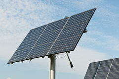 Renewable Energy - Photovoltaic Solar Panel Arrays. Photovoltaic solar panel arrays with blue sky and white clouds in the background Stock Image