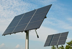 Renewable Energy - Photovoltaic Solar Panel Arrays. Photovoltaic solar panel arrays with blue sky and white clouds in the background Royalty Free Stock Photo