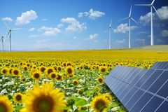Renewable energy resources in natural environment with sunflower field, photovoltaic panels and windmills stock image