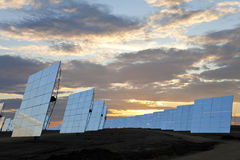Renewable Energy Solar Mirror Panels at Sunset. A field of solar mirror panels harnessing the sun's rays to provide alternative green energy stock image