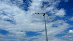 Renewable energy - wind mill turbines. Windmill rotating during windy summer cloudy day with cloudy blue sky as a background stock footage