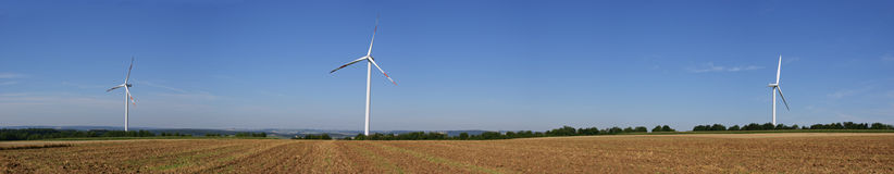 Renewable energy from wind turbines. Three power generating wind turbines in the German countryside. Panoramic view with lot of copy space Royalty Free Stock Image