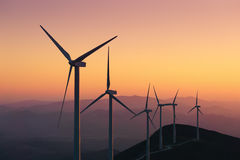 Renewable energy with wind turbines. At sunset Stock Photos