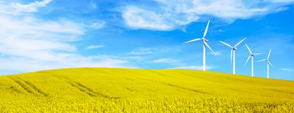 Renewable energy with wind turbines in yellow flowers hills. Ecology environmental background for presentations and websites. Beautiful summer wallpaper stock photography