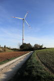 Renewable energy. With a wind wheel on a field Royalty Free Stock Photos