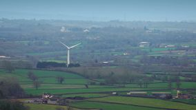 Windmill Rotating In The Countryside. Renewable energy windmill in misty countryside stock video footage