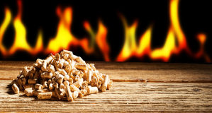 Renewable or sustainable energy concept. With a row of burning flames behind a heap of natural wood pellets in a panorama view with copy space Royalty Free Stock Image