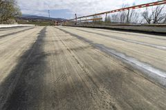 Blacktop stripes on the ground base. Renewal of bridge over the channel near Cetina river, groundwork prepared for asphalt Stock Photo