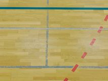 Renewal wooden floor of sports hall with colorful marking lines and new lacquered surface. White black red lines blue playfield in sports hall Royalty Free Stock Photography