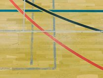Renewal wooden floor of sports hall with colorful marking lines and new lacquered surface. White black red lines blue playfield in sports hall Royalty Free Stock Image