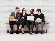 Renforcement d'équipe, équipe multi-ethnique s'asseyant sur la réunion images stock