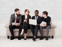 Renforcement d'équipe, équipe multi-ethnique s'asseyant sur la réunion photo stock