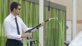 Rengörande automatisk för yrkesmässig manlig chaufför för affärsgrupp på självbetjäningbiltvätt stock video