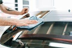 Rengörande fönster för man med en blå filt av en tonad bil arkivbild