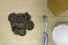 Rengörande gamla mynt grundar vid en metalldetektor royaltyfria foton