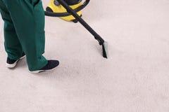 Rengörande matta för man med dammsugare, closeup royaltyfri fotografi