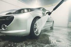 Rengörande medel för man med den högtryckvattensprej eller strålen Biltvättdetaljer tvätt av framhjulet av en bil arkivfoto