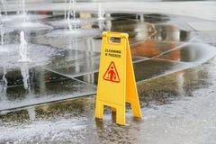 Rengörande pågående vått område för varningstecken nära Arkivbild
