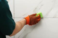 Reng?rande skarv f?r man mellan keramiska tegelplattor med svampen p? wal Byggnads- och renoveringarbeten royaltyfria foton
