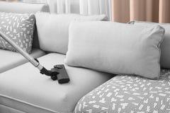Rengörande soffa med dammsugare royaltyfria foton