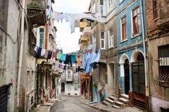Rengöringen beklär uttorkning på ett rep mellan gamla hus av den smala gatan Arkivbilder
