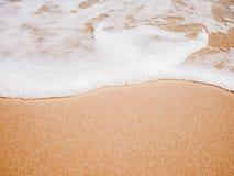 Rengöringen och vit vinkar på stranden Arkivbilder