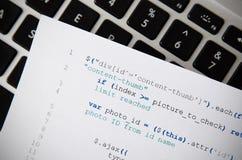 Rengöringsdukbärare som programmerar kod, skrivev ut på ett stycke av papper Arkivfoton