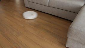 Reningsteknikmaskin i vardagsrum på brunt golv Smart robotdammsugare arkivfilmer
