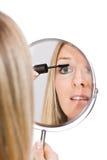 Renivellement de femme dans le miroir photographie stock