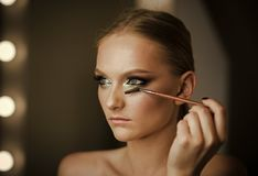 Renivellement professionnel La femme appliquent le maquillage de mascara sur des cils, regardent Brosse d'applicateur de mascara  photo libre de droits