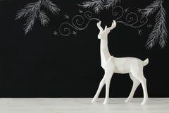 Renna bianca sulla tavola di legno sopra le illustrazioni disegnate a mano del gesso del whith del fondo della lavagna Immagine Stock